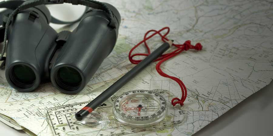 Plat Map on Table with Compass and Binoculors
