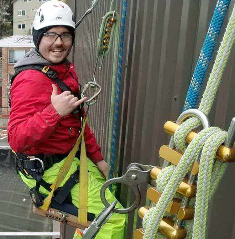 Charter Construction - A worker resting mid rappel on the side of a building during the construction process